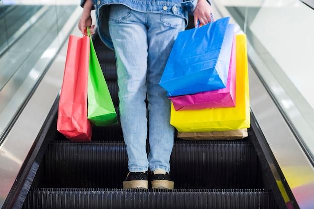Pessoa, com, bolsas para compras, ligado, a, escada rolante