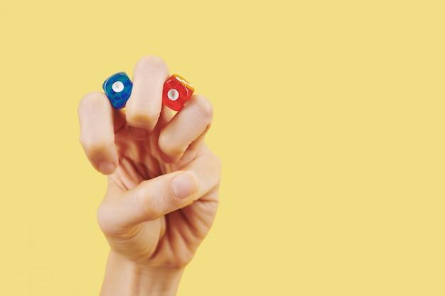 Pessoa com dados vermelhos e azuis entre os dedos