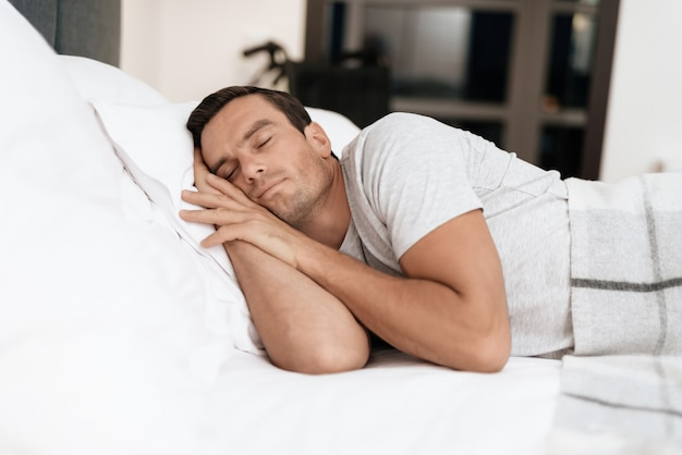 Pessoa com deficiência dorme na cama com lençóis brancos.