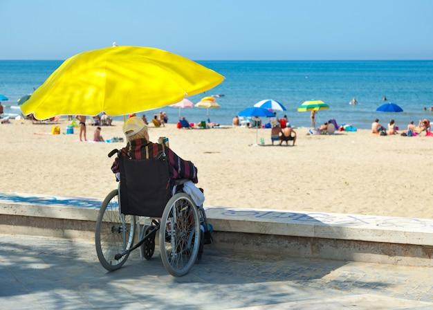 Pessoa com deficiência em cadeira de rodas não pode acessar a praia.