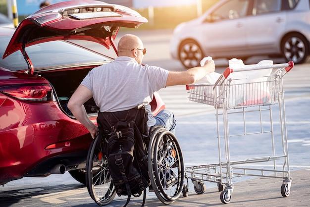 Pessoa com deficiência física coloca as compras no porta-malas de um carro no estacionamento de um supermercado