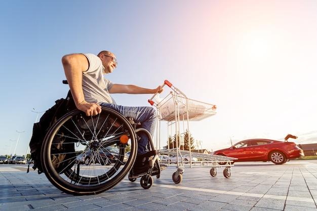 Pessoa com deficiência física empurra um carrinho em direção a um carro no estacionamento de um supermercado