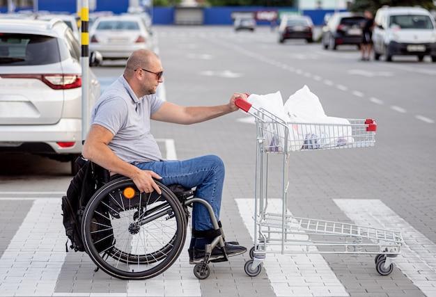 Pessoa com deficiência física empurrando carrinho na frente de si no estacionamento de um supermercado