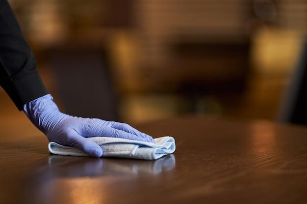 Pessoa com luvas para limpar e higienizar uma mesa de madeira