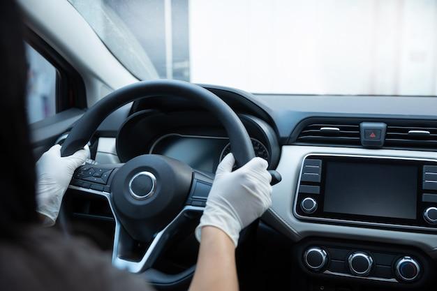 Pessoa com mãos enluvadas dentro de carro