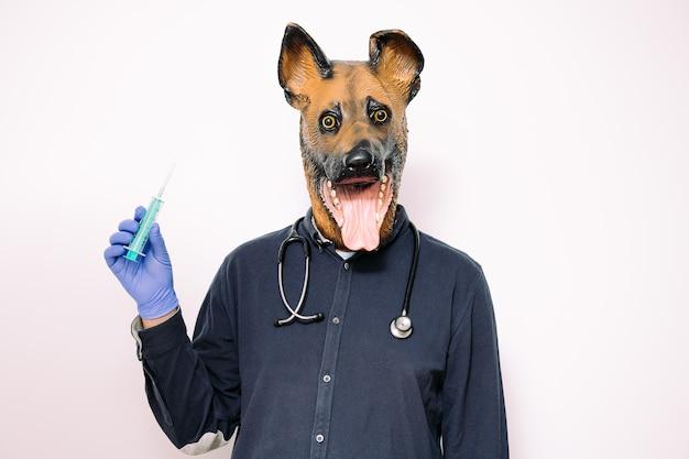 Pessoa com máscara de cachorro mostra uma seringa