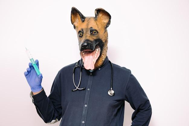 Pessoa com máscara de cachorro mostrando uma seringa