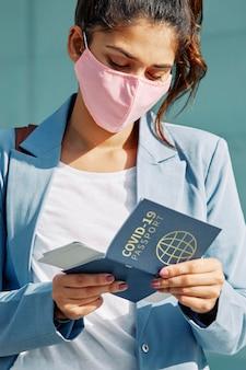 Pessoa com máscara segurando passaporte de saúde