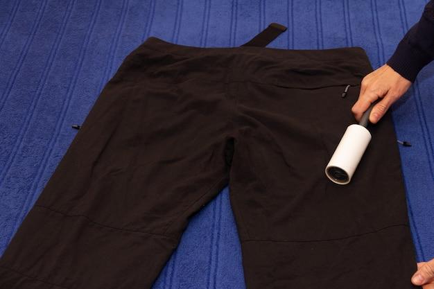 Pessoa com rolo pegajoso para limpar roupas, limpar calças pretas