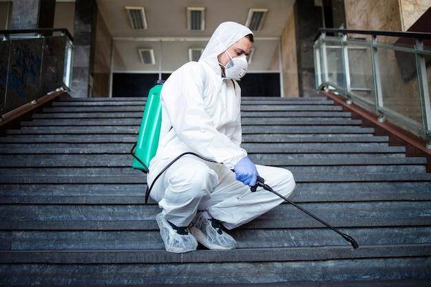 Pessoa com roupa de proteção química branca desinfetando corredores públicos e medidas para impedir a propagação do vírus corona altamente contagioso