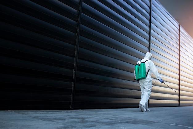 Pessoa com roupa de proteção química branca fazendo a desinfecção de áreas públicas para impedir a propagação do vírus corona altamente contagioso