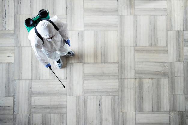 Pessoa com roupa de proteção química branca fazendo a desinfecção de áreas públicas para interromper a pulverização do vírus corona altamente contagioso
