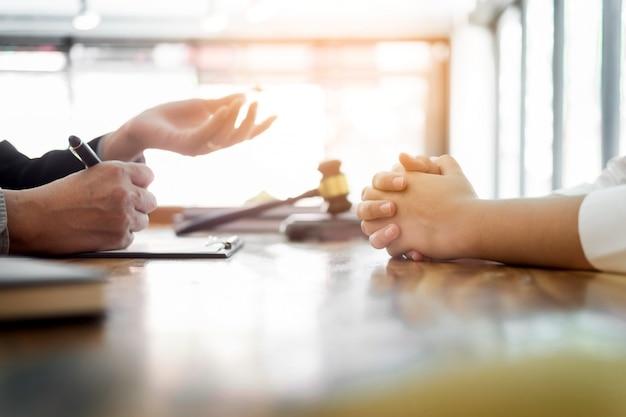 Pessoa com um advogado que discute documentos de contrato sentados à mesa