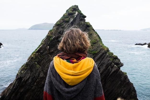 Pessoa com um capuz em pé na frente de uma enorme formação rochosa perto do mar