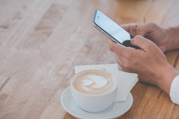 Pessoa com um smartphone e um café