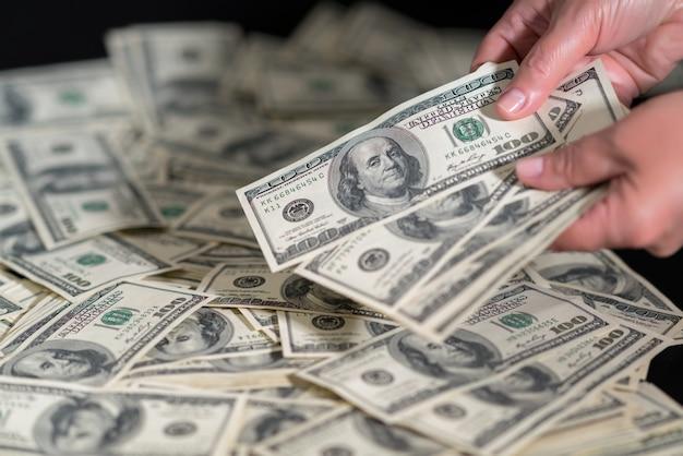 Pessoa contando notas de 100 dólares em uma pilha, espalhada sobre uma mesa em um close-up nas mãos