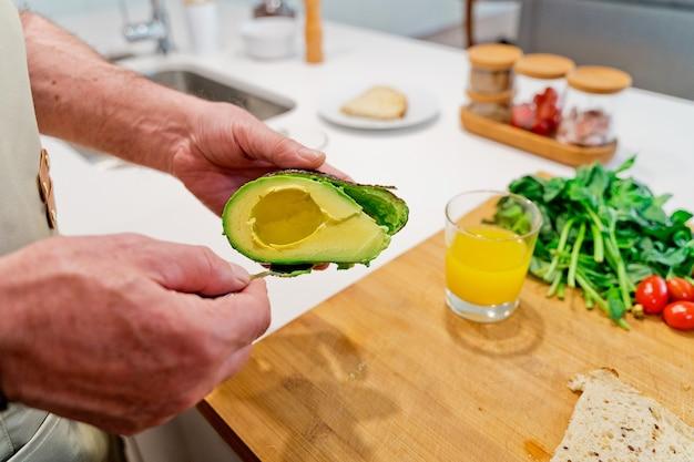 Pessoa cortando um abacate na cozinha.