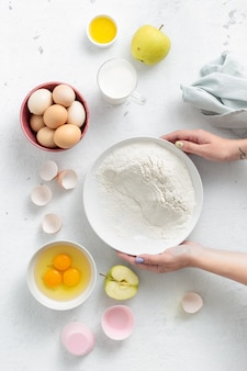 Pessoa cozinhar sobremesa. mãos de mulheres preparando torta de maçã vista superior. ingredientes alimentares