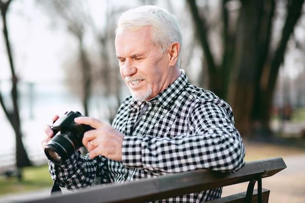 Pessoa criativa. homem maduro bonito usando a câmera e olhando para baixo