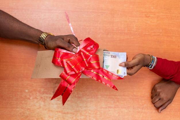 Pessoa dando a um amigo um presente em dinheiro em um envelope.