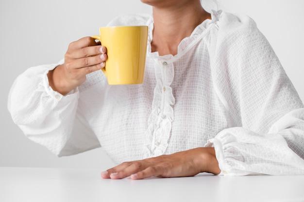 Pessoa de camisa branca, segurando uma xícara
