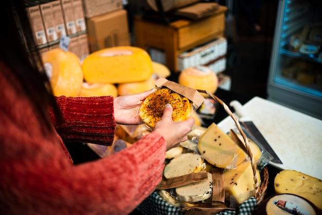 Pessoa de close-up com arranjo de queijo