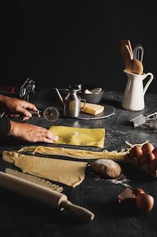 Pessoa de close-up com cortador de pizza e utensílios