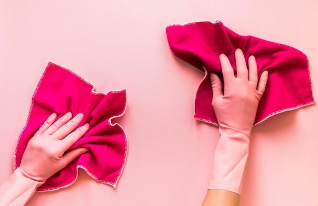Pessoa de close-up com luvas cor de rosa e panos