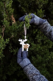 Pessoa de close-up com luvas para decorar a árvore de natal com enfeite