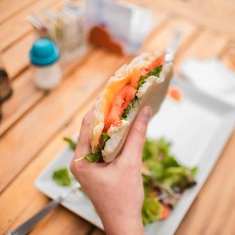 Pessoa de close-up com saboroso sanduíche