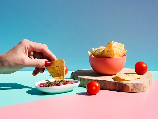 Pessoa de close-up com tortilla chips e molho