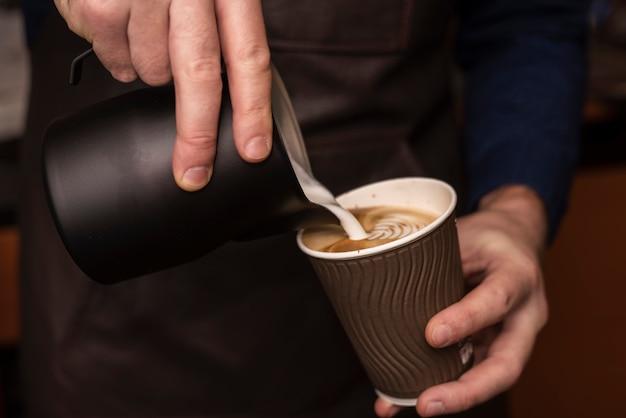 Pessoa de close-up derramando leite na xícara de café