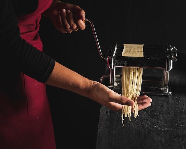 Pessoa de close-up fazendo macarrão com máquina
