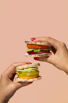 Pessoa de close-up segurando dois hambúrgueres vegetarianos