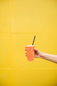Pessoa de close-up, segurando o copo de suco