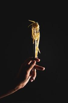 Pessoa de close-up, segurando o garfo com macarrão