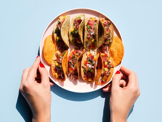 Pessoa de close-up, segurando o prato com tacos