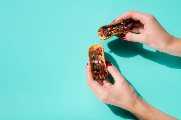 Pessoa de close-up segurando pequenas tacos com cópia-espaço
