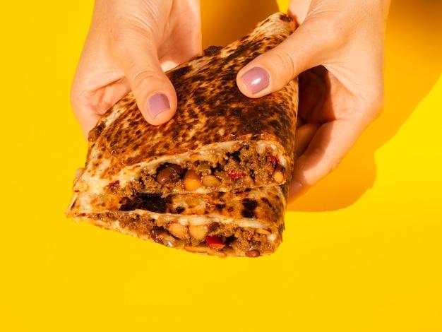 Pessoa de close-up segurando saborosa comida mexicana