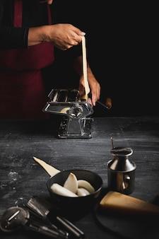 Pessoa de close-up usando a máquina para fazer macarrão