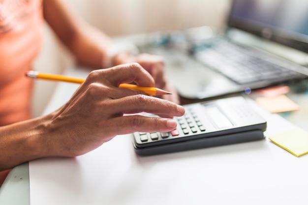 Pessoa de colheita fazendo cálculos perto de laptop