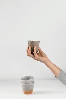 Pessoa de cozinha mínima abstrata segurando xícara