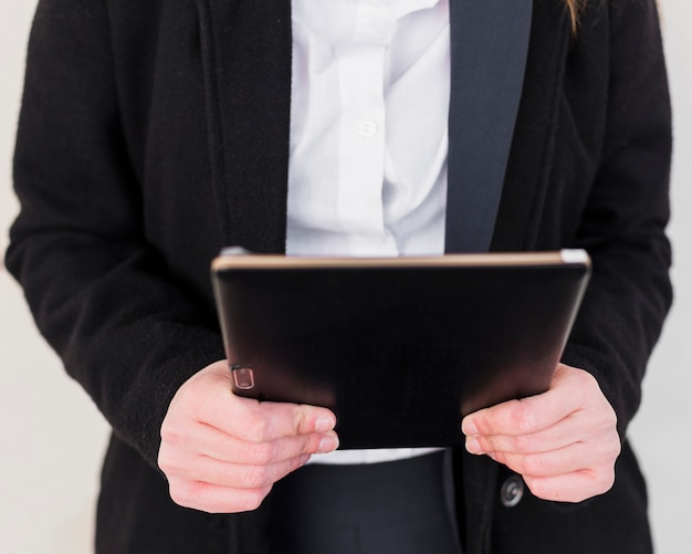 Pessoa de jaqueta preta usando tablet