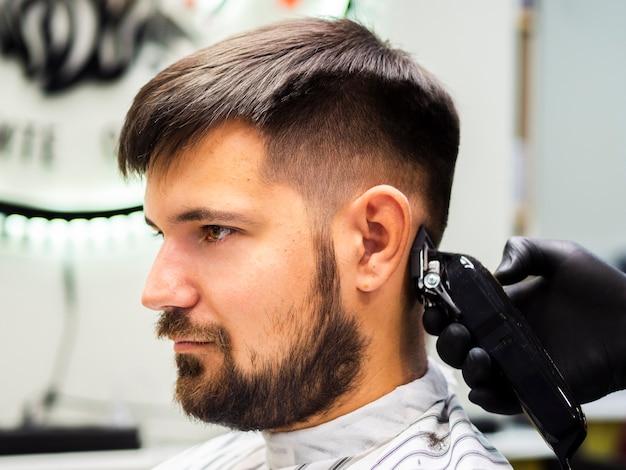 Pessoa de lado recebendo um novo corte de cabelo