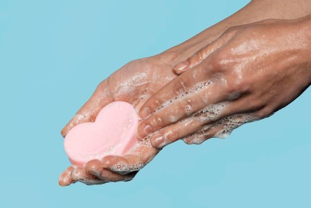 Pessoa de lado segurando um sabonete em forma de coração