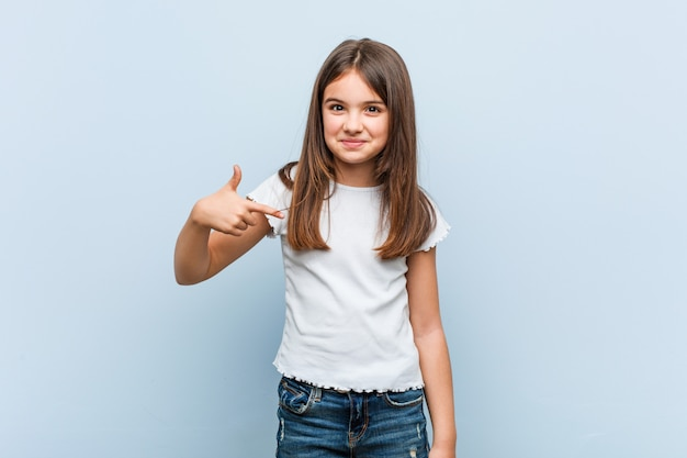 Pessoa de menina bonito, apontando à mão para um espaço de cópia de camisa