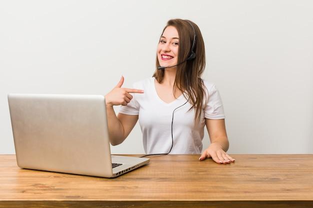 Pessoa de mulher jovem operador de telemarketing apontando à mão para um espaço de cópia de camisa, orgulhoso e confiante