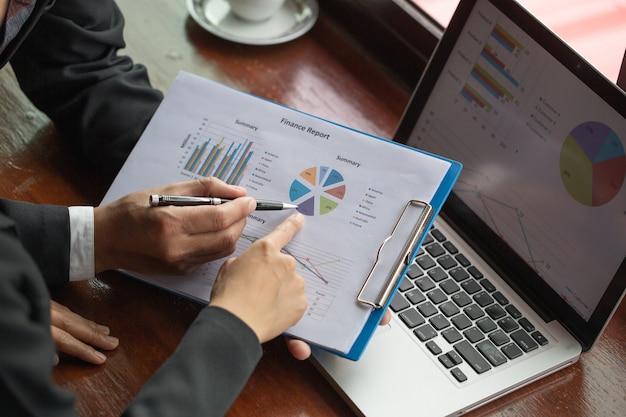 Pessoa de negócios, analisando as estatísticas financeiras exibidas no papel de gráfico