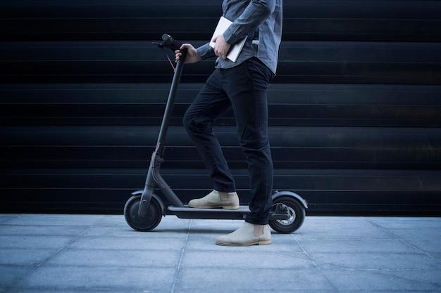 Pessoa de negócios com computador tablet em seu veículo de transporte de scooter elétrico