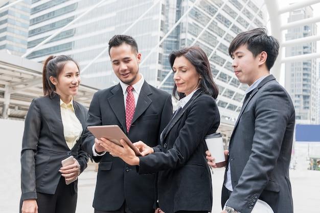 Pessoa de negócios do grupo se reunindo com procurando consultar tablet para trabalho na cidade